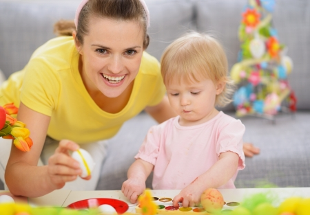 Happy mother and baby making Easter decorations Stock Photo - 17304819