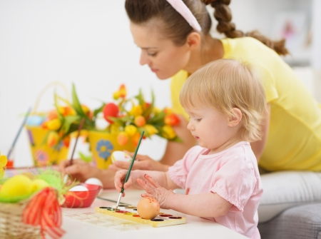 Mother and baby making Easter decorations photo