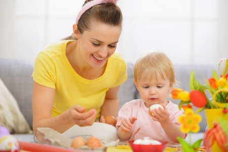 Happy mother and baby eating Easter eggs Stock Photo