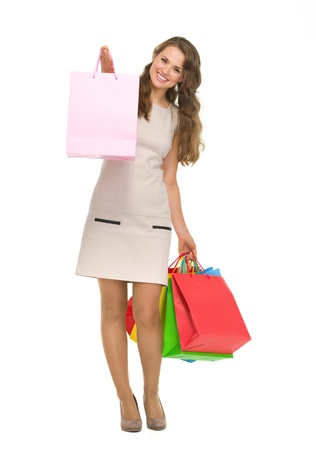 Full length portrait of happy young woman showing shopping bags Stock Photo - 17382859