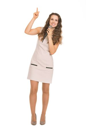 Happy young woman with microphone pointing up on copy space Stock Photo - 17382850