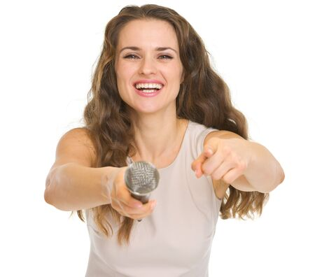 Happy young woman giving microphone and pointing in camera Stock Photo - 17382834