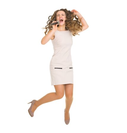Happy young woman jumping and singing with microphone photo
