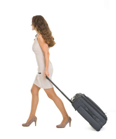 Young woman walking with wheels suitcase. Side view photo