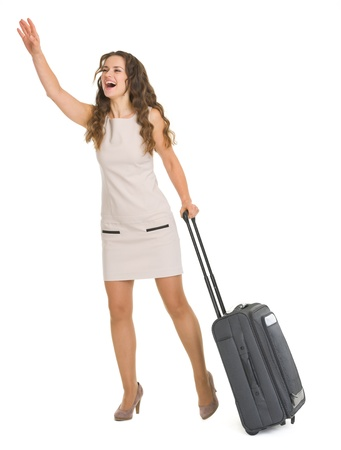 Young woman with wheels suitcase catching taxi Stock Photo - 17382857