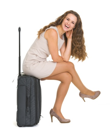 Smiling young woman sitting on wheels suitcase Stock Photo - 17382826
