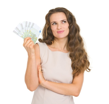 Thoughtful young woman holding fun of euro banknotes Stock Photo - 17382835