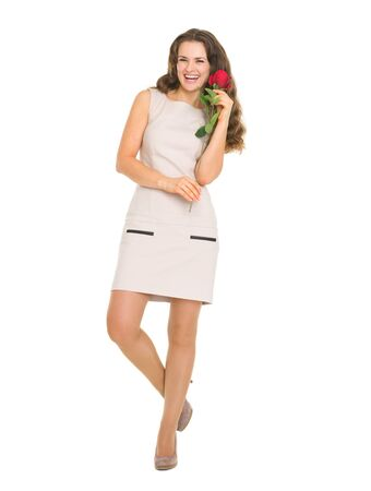 Full length portrait of smiling young woman with red rose photo