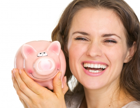Portrait of smiling young woman holding piggy bank Stock Photo - 17418545