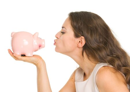 Young woman kissing piggy bank photo