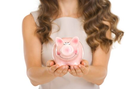 frugality: Closeup on piggy bank in woman hands