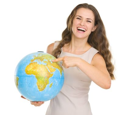 Smiling young woman pointing on globe photo