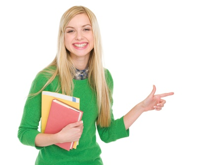 Smiling student girl with books pointing on copy space Stock Photo - 17417884