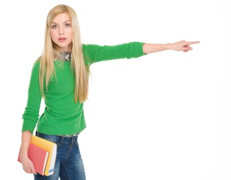 Surprised student girl with books pointing on copy space Stock Photo - 17417881