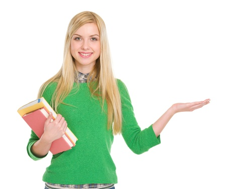 youthfulness: Smiling student girl with books showing something on palm