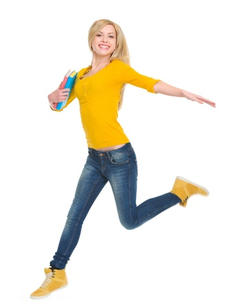 Smiling student girl with books jumping photo