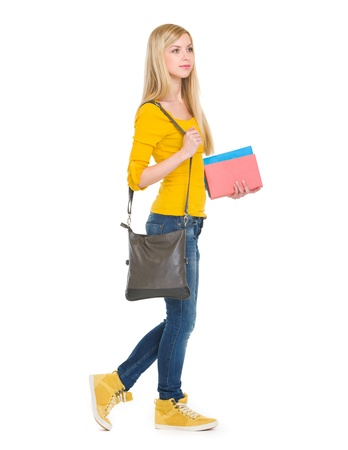 youthfulness: Teenage student girl with books going sideways