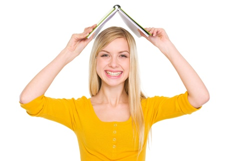 classbook: Smiling student girl making roof with book