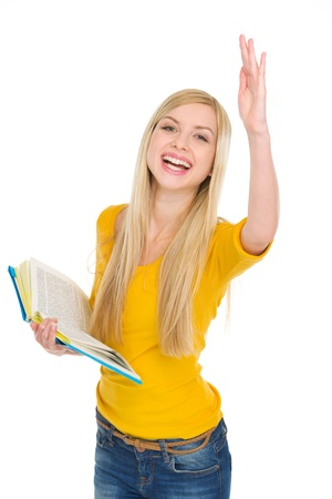 classbook: Happy student girl with book rising hand to answer Stock Photo
