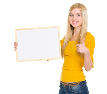Happy student girl showing blank board and thumbs up photo