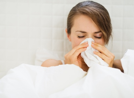 Woman with flu laying in bed photo