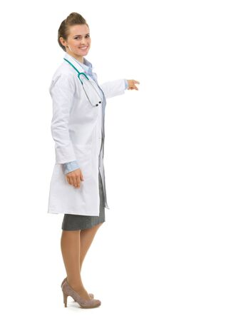 Full length portrait of medical doctor woman pointing on copy space Stock Photo - 17563383