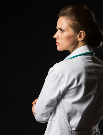 authoritative woman: Portrait of confident medical doctor woman looking on copy space isolated on black