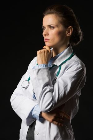 Portrait of thoughtful medical doctor woman looking on copy space isolated on black Stock Photo - 17563289