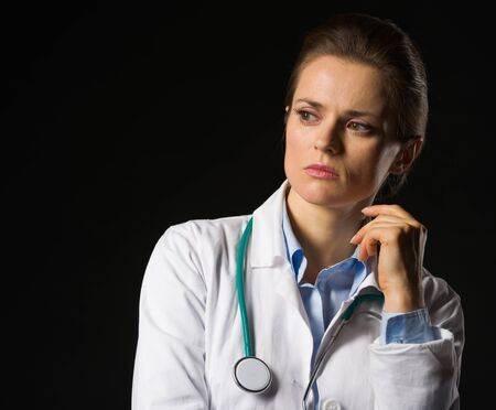 Portrait of thoughtful medical doctor woman looking on copy space isolated on black Stock Photo - 17563290