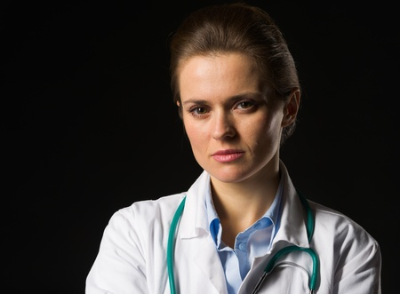Portrait of confident medical doctor woman isolated on black Stock Photo - 17563279