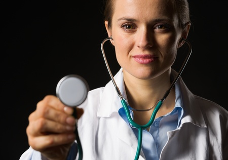 Medical doctor woman using stethoscope isolated on black Stock Photo - 17563281