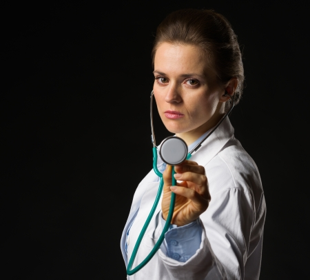 Confident medical doctor woman using stethoscope isolated on black photo