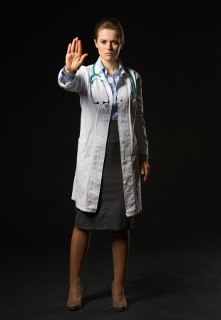 Full length portrait of medical doctor woman showing stop gesture on black background Stock Photo - 17563276