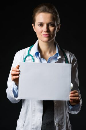 Medical doctor woman showing blank billboard isolated on black Stock Photo - 17563286