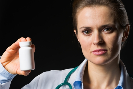 Medical doctor woman showing medicine bottle on black background Stock Photo - 17563266