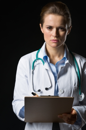 Portrait of confident medical doctor woman with clipboard photo