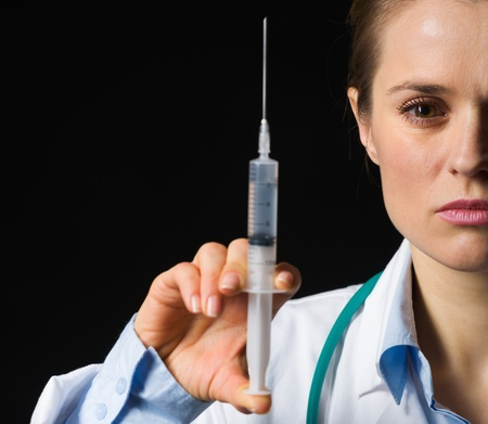 Closeup on medical doctor woman holding syringe isolated on black photo