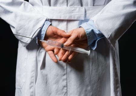 Closeup on medical doctor woman hiding syringe behind back Stock Photo - 17563284