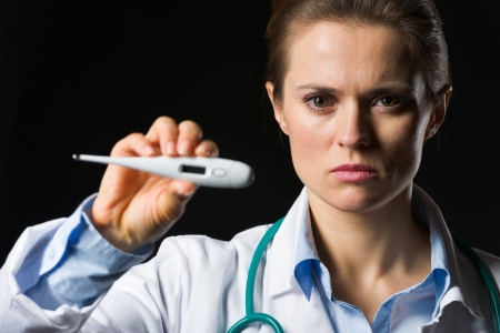 authoritative woman: Medical doctor woman showing thermometer isolated on black Stock Photo