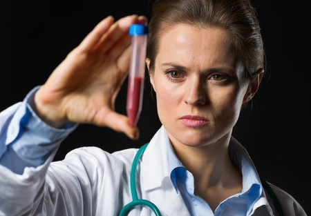 Medical doctor woman looking on test tube with blood isolated on black Stock Photo - 17563272