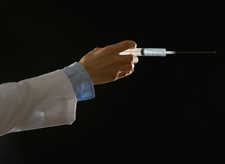 Closeup on hand of medical doctor with syringe isolated on black photo