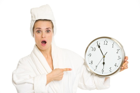tardiness: Surprised young woman in bathrobe pointing on clock