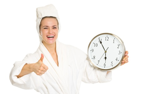 Smiling young woman in bathrobe showing clock and thumbs up Stock Photo - 17669660