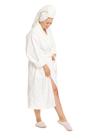 Full length portrait of happy young woman in bathrobe looking on leg photo