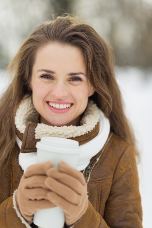 Happy young woman with hot beverage in winter outdoors Stock Photo - 17797425