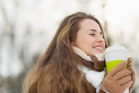 Happy young woman enjoying hot beverage in winter park Stock Photo - 17797374