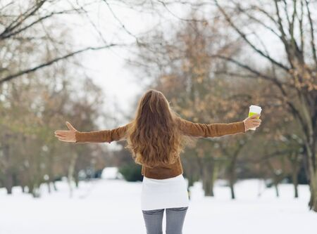 Young woman with hot beverage in winter park. Rear view photo