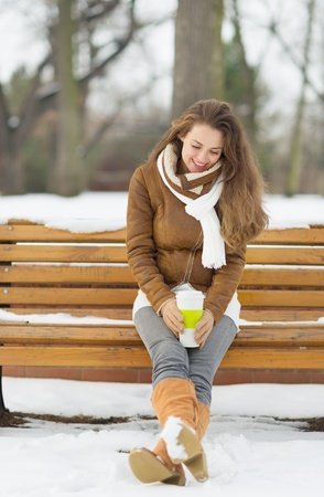 Happy young woman sitting on bench with hot beverage in winter outdoors Stock Photo - 17797379