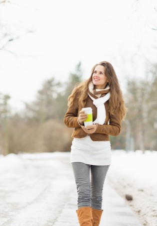winter thaw: Happy young woman with hot beverage walking in winter park