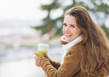 Portrait of happy young woman with hot beverage photo